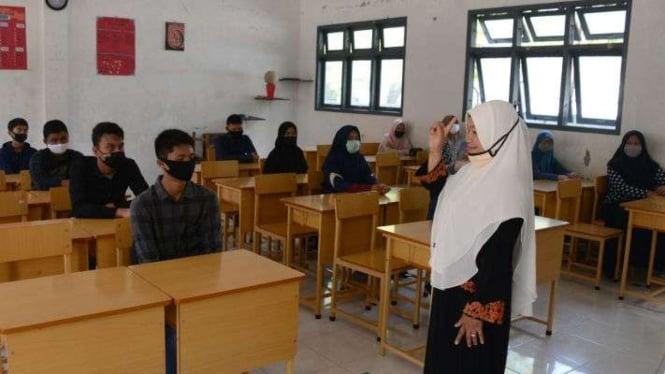Seorang guru memberikan arahan kepada murid baru dalam ruangan kelas dengan pembatasan jaga jarak saat simulasi penerapan protokol kesehatan di SMA-1 Banda Aceh, Aceh, Sabtu (11/7/2020). (Foto Ilustrasi)