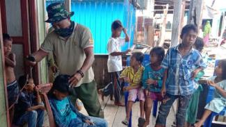 VIVA Militer : Seorang prajurit TNI mendadak jadi tukang cukur di lokasi TMMD