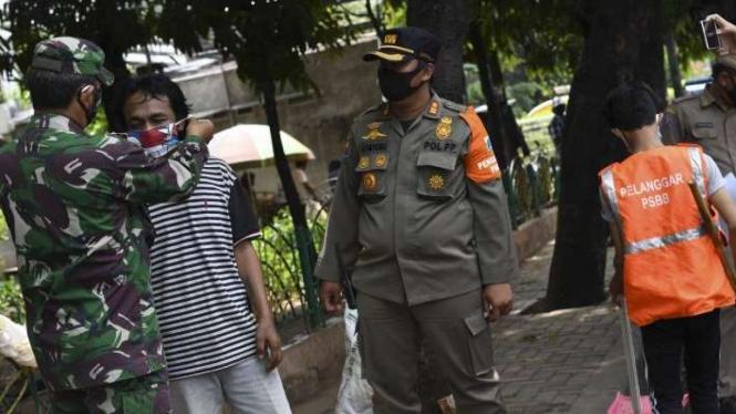 Petugas gabungan memasangkan masker kepada seorang warga (Foto ilustrasi)