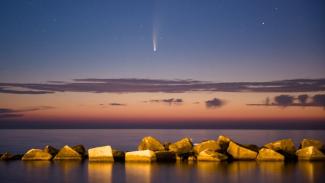 Komet Neowise, tampak di atas Pelabuhan Molfetta, Italia. Lintasan terdekatnya dengan Bumi akan terjadi pada 23 Juli.-Getty Images