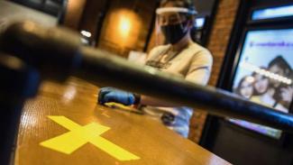 Pekerja memasang tanda jaga jarak saat simulasi pembukaan dan peninjauan tempat hiburan bioskop. (Foto ilustrasi)