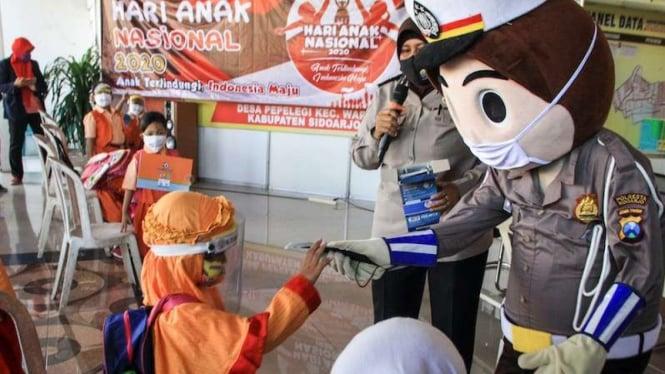 Badut Polisi memberikan masker kepada anak-anak dalam rangka peringatan Hari Anak Nasional di Balai Desa Pepelegi, Waru, Sidoarjo, Jawa Timur, Rabu (22/7/2020). Peringatan Hari Anak Nasional 23 Juli 2020 bertema