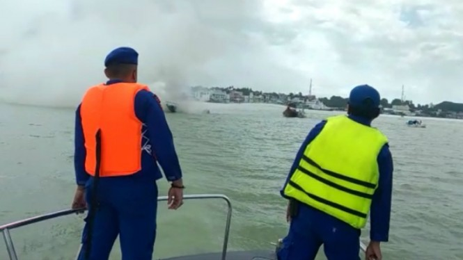 Petugas menyaksikan kapal terbakar dan tenggelam
