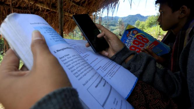 Para siswa belajar online di atas puncak bukit.