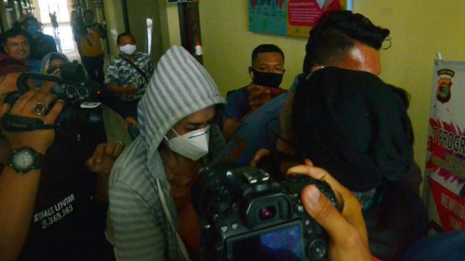 Personel kepolisian membawa artis berinisial VS (tengah) saat akan menjalani pemeriksaan di Polresta Bandar Lampung, Lampung, Rabu (29/7/2020).