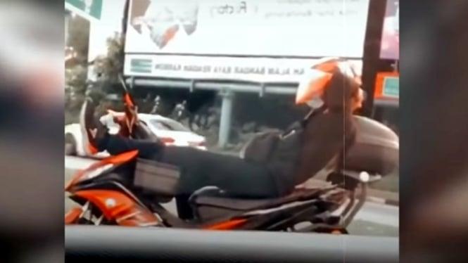 Pemotor bersitirahat sejenak di lampu lalu lintas
