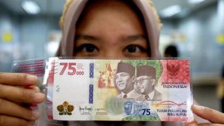 Warga melakukan penukanan uang khusus edisi HUT RI Rp75 ribu.