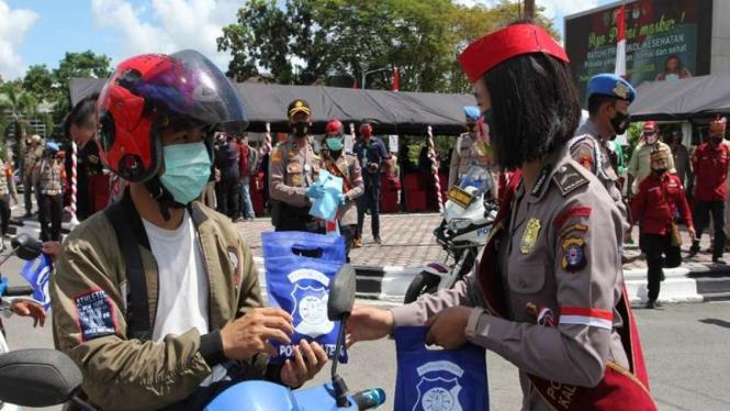 Kampanye protokol kesehatan dengan membagikan masker