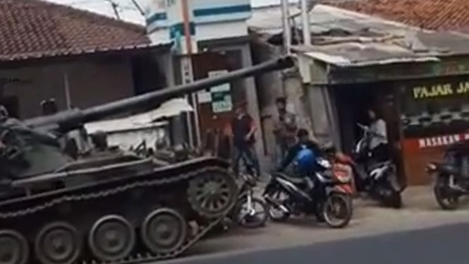 Pria memindahkan motor usai kecelakaan tank