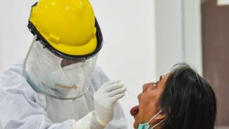 Tenaga medis melakukan tes usap atau swab test.