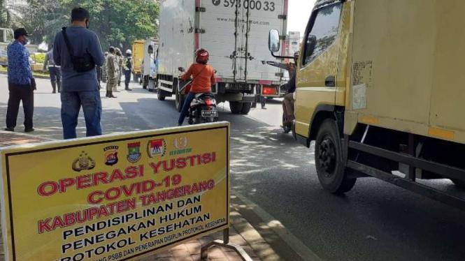 Lalu lintas di satu ruas jalan di Kabupaten Tangerang, Banten, selama penerapan kebijakan Pembatasan Sosial Berskala Besar (PSBB) untuk pengendalian wabah virus corona.