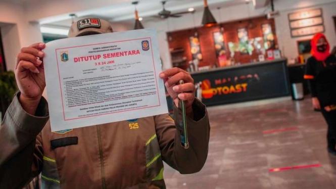 Petugas Satpol PP menutup restoran yang menyediakan layanan makan di tempat saat razia PSBB Jakarta di kawasan Sunter Agung, Jakarta, Kamis (24/9/2020).