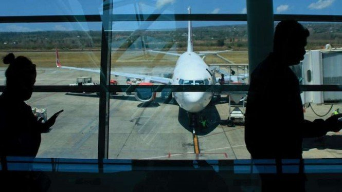 Calon penumpang di bandara berjalan menuju pesawat terbang komersil. (Foto ilustrasi)