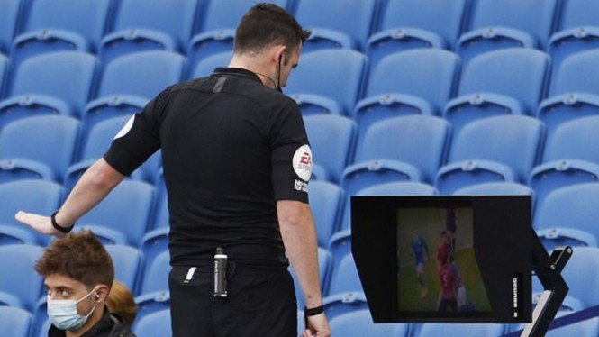 Wasit Brighton vs MU sedang meninjau VAR setelah laga berakhir.
