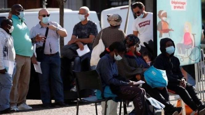 Warga Prancis di Paris saat menunggu bus di tengah pandemi COVID-19.