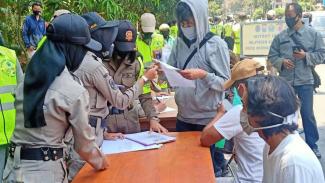 Aparat gabungan dalam operasi yustisi untuk mendisiplinkan warga dalam menerapkan protokol kesehatan pencegahan penularan COVID-19, terutama memakai masker, di Kota Malang, Jawa Timur.