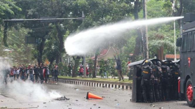 Polisi menembakkan meriam air ke arah massa yang berunjuk rasa menentang Undang-Undang Omnibus Law Cipta Kerja di depan Gedung DPRD Sumatera Utara, Kota Medan, Kamis siang, 8 Oktober 2020.