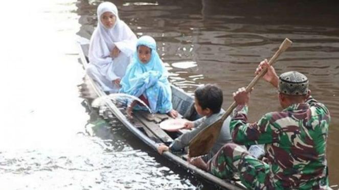 VIVA Militer: Koptu TNI Syahdan Shaleh jemput anak-anak pakai sampan.