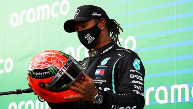 Pembalap Mercedes, Lewis Hamilton, menerima helm keramat Michael Schumacher
