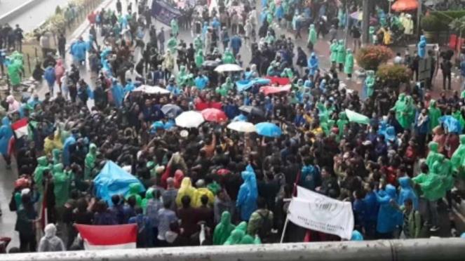 Mahasiswa tetap melanjutkan aksi demonstrasi meski hujan mengguyur.