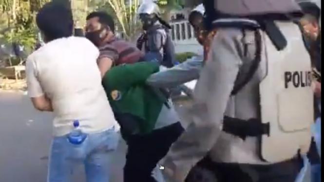 Tangkapan layar video polisi berseragam ribut dengan polisi pakaian bebas.