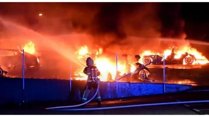 Petugas Pemadam Kebakaran memadamkan mobil listrik yang terbakar.