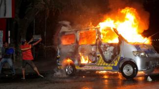 Warga berusaha padamkan ambulans yang dibakar massa pendemo di Makassar
