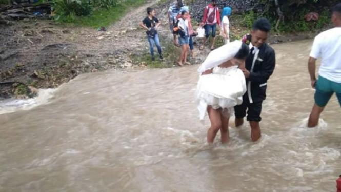 Pasangan calon pengantin menerjang banjir.