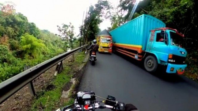 Pemotor lempar botol air mineral ke truk
