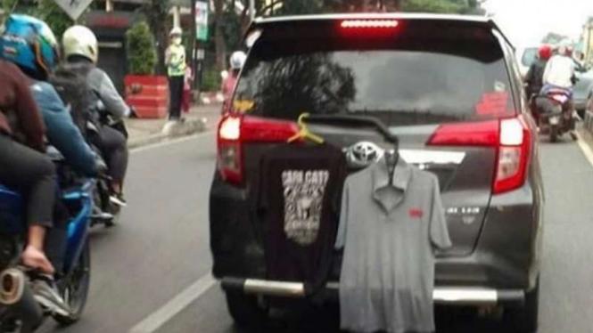 Ada dua kaos menggantung di wiper belakang Toyota Calya