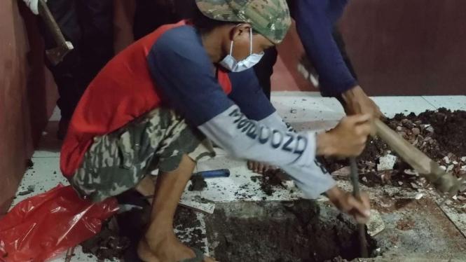 Polisi dibantu beberapa warga berhasil mengevakuasi sesosok jasad yang dikubur di dalam rumah kontrakan di kawasan Gang Kopral Daman, Kecamatan Sawangan, Depok, Jawa Barat.