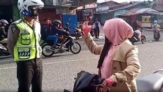 Emak-emak memaki polisi saat ditegur karena tidak memakai helm. (Foto ilustrasi).