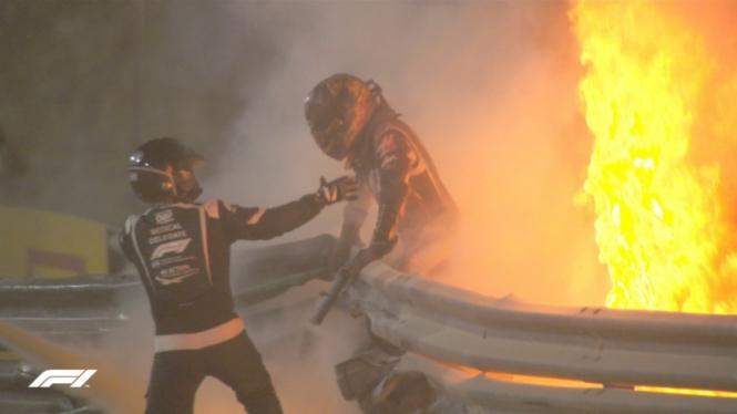 Pembalap tim Haas, Romain Grosjean, sedang diselamatkan usai mobilnya terbakar.