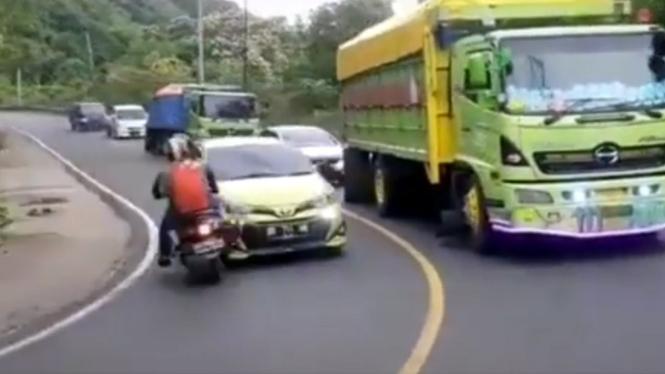 Mobil Yaris salip truk dan ditabrak motor