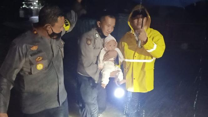 Petugas polisi mengevakuasi seorang bayi ketika banjir melanda Kelurahan Jombang Wetan, Kota Cilegon.