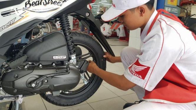 Mekanik memeriksa ban motor