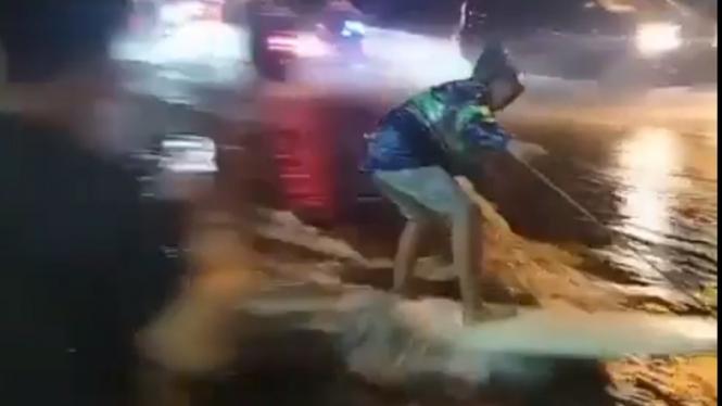 Warga Bali main selancar di jalanan yang tergenang banjir.