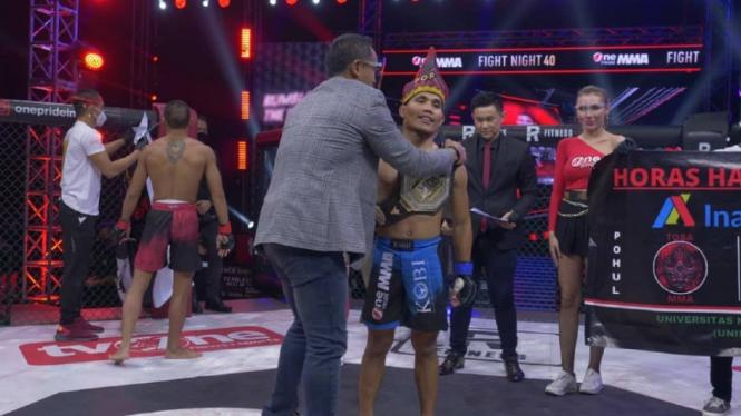 Ketua KOBI, Anindra Ardiansyah Bakrie, mengalungkan sabuk juara ke Adi Rominto