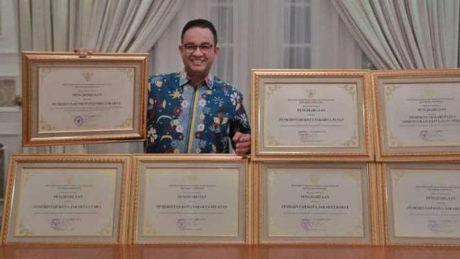 Gubernur DKI Jakarta, Anies Baswedan, berfoto bersama sejumlah penghargaan.