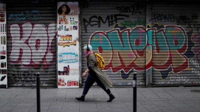 Seorang warga dengan memakai masker berjalan melewati salon rambut dan toko kosmetik yang tutup di sebuah jalan di Paris, Prancis, Kamis (19/11/2020), saat pembatasan diberlakukan untuk kedua kalinya akibat wabah penyakit virus corona (COVID-19).