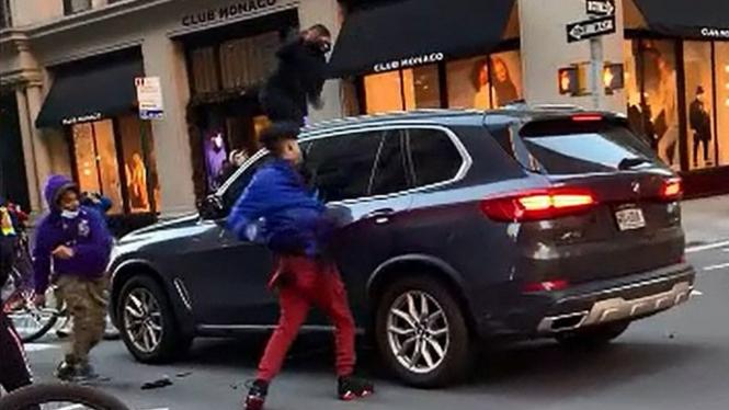 Para pengendara sepeda merusak mobil BMW.