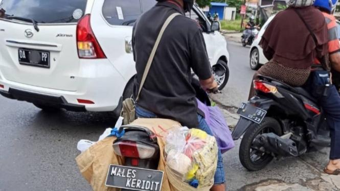 Plat nomor Males Keridit di sepeda motor bebek.