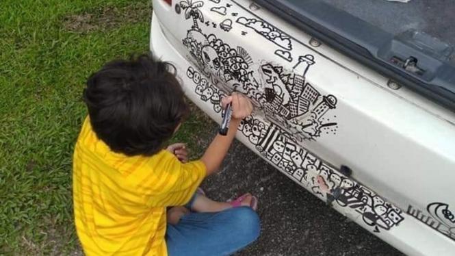 Bocah melukis doodle di bodi mobil.