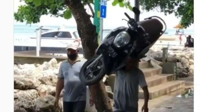 Viral video pria menggendong skuter matik.