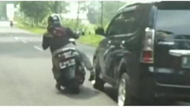 Pengendara motor nyaris terserempet mobil.