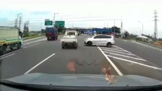 Mobil Datsun tertangkap kamera dasbor sedang putar balik di jalan tol.
