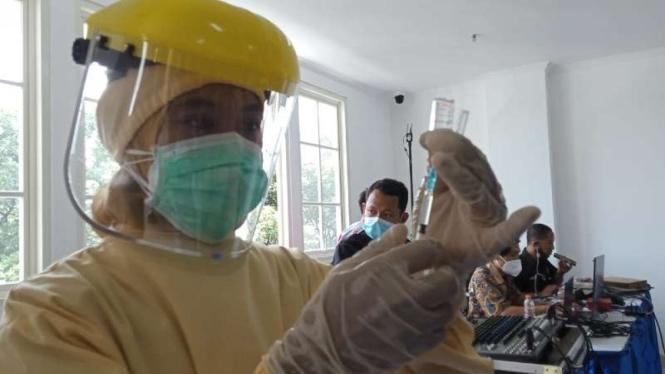 Ilustrasi Seorang petugas kesehatan bersiap menyuntikkan vaksin COVID-19 untuk para tenaga kesehatan.