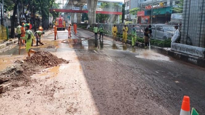Petugas membersihkan sisa lumpur akibat banjir di Jalan Kapten Tendean Mampang