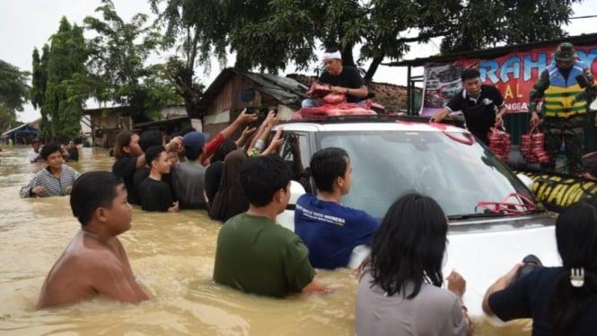 Anggota DPR RI Dedi Mulyadi membagikan nasi kotak korban banjir di Karawang