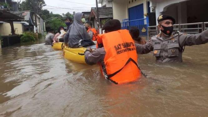 Petugas kepolisian membantu mengevakuasi warga yang kebanjiran di Rawa Buaya.